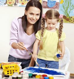 teacher teaching the girl on how to paint
